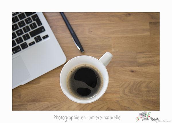 Une tasse à café posée sur une table avec un ordinateur. Espace de travail. Mise en scène au bureau.